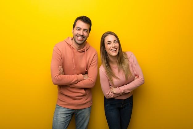 Grupo de duas pessoas em fundo amarelo, mantendo os braços cruzados, enquanto sorrindo