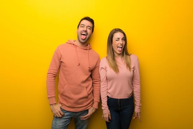 Grupo de duas pessoas em fundo amarelo mostrando a língua para a câmera