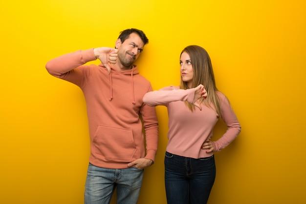 Grupo de duas pessoas em fundo amarelo, mostrando o polegar baixo sinal