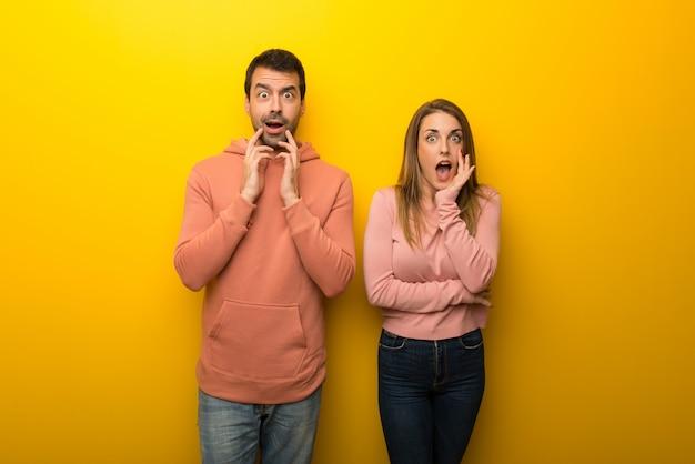 Grupo de duas pessoas em fundo amarelo surpreso e chocado ao olhar para a direita
