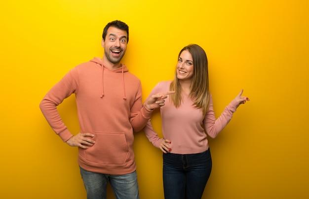 Grupo de duas pessoas no dedo apontando fundo amarelo para o lado