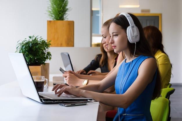 Grupo de empresária bonita trabalhando em conjunto com o novo projeto de inicialização usando o laptop no apartamento moderno