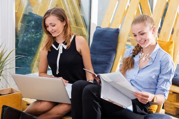 Grupo de empresária bonita trabalhando em conjunto com o novo projeto de inicialização usando o laptop no apartamento moderno Foto Premium