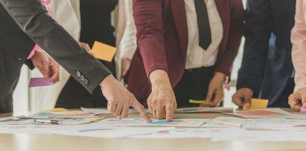 Grupo de empresárias irreconhecíveis, reunindo-se em um brainstorming na mesa de trabalho, apontando o dedo e analisando o gráfico e o gráfico de dados com autoconfiança e troca plena de conhecimento em equipe.