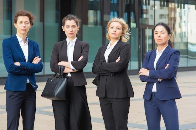 Grupo de empresárias sérias com os braços cruzados em pé juntos perto do prédio de escritórios, posando, olhando para a câmera. vista frontal. equipe de negócios ou conceito de trabalho em equipe