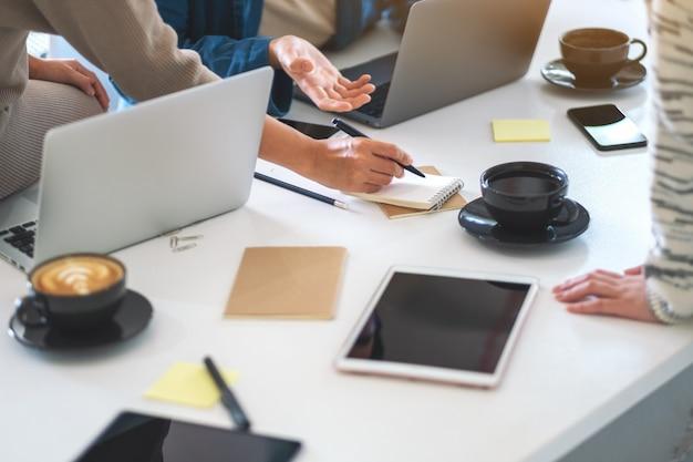 Grupo de empresário discutindo e escrevendo no caderno com o laptop na mesa do escritório