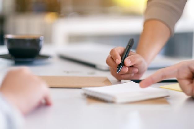 Grupo de empresário discutindo e escrevendo no caderno sobre a mesa do escritório