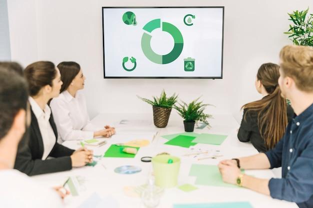 Grupo de empresários a olhar para o ícone de recursos naturais em reunião