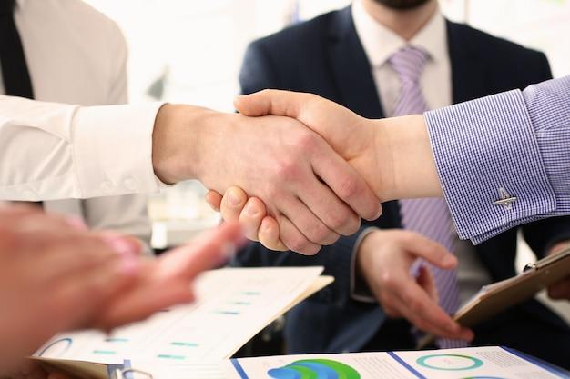 Grupo de empresários, apertando as mãos após reunião produtiva