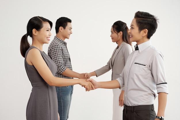 Grupo de empresários asiáticos, apertando as mãos no estúdio