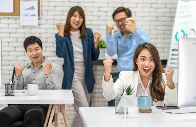 Grupo de empresários asiáticos comemorando e mostrando o polegar para cima com felicidade Foto Premium