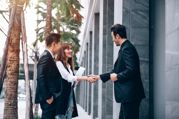 Grupo de empresários asiáticos no distric de negócios falando sobre novos negócios e economia em local ao ar livre