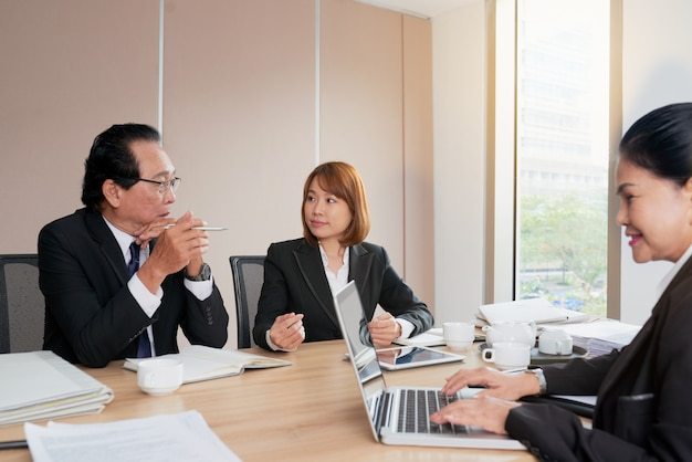 Grupo de empresários asiáticos, sentados ao redor da mesa de reunião e falando