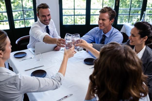 Grupo de empresários brindando o copo de água no restaurante