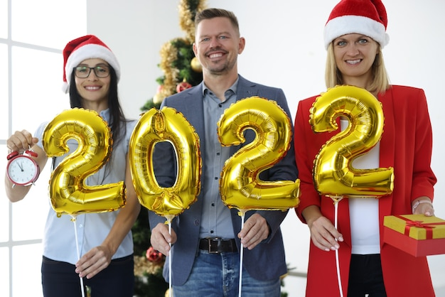 Grupo de empresários com chapéus de papai noel segurando balões dourados com números 2022 perto da árvore do ano novo. conceito corporativo de feriados de ano novo