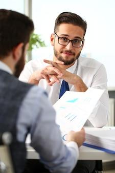 Grupo de empresários com gráfico financeiro e caneta de prata