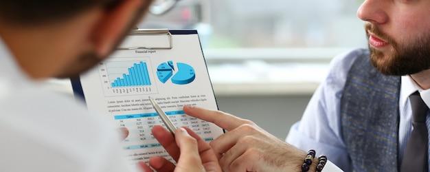 Grupo de empresários com gráfico financeiro e caneta prata