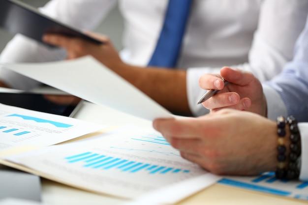 Grupo de empresários com gráfico financeiro e caneta prateada