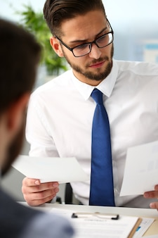 Grupo de empresários com gráfico financeiro no braço resolve e discute o problema