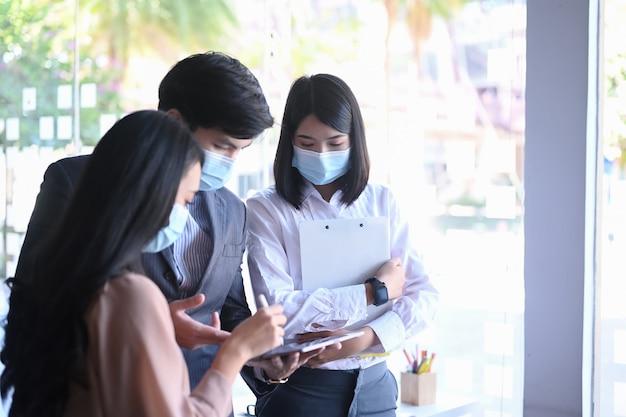 Grupo de empresários com máscara protetora trabalhando e se comunicando durante uma reunião no escritório.