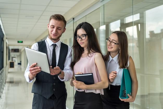 Grupo de empresários com papelada na reunião antes do árduo dia de trabalho no corredor do escritório. trabalho em equipe