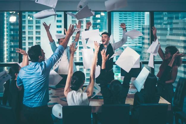 Grupo de empresários comemorando jogando seus papéis de negócios no ar