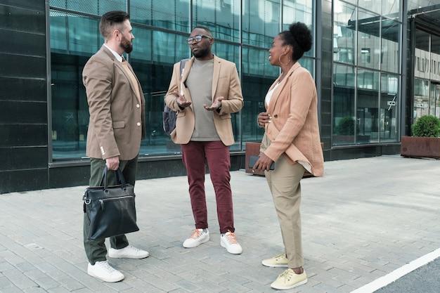 Grupo de empresários conversando perto de um prédio comercial na cidade