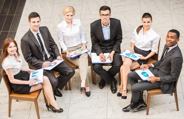 Grupo de empresários de terno sentado em círculo.