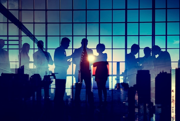 Grupo de empresários debatendo com a silhueta do pôr do sol