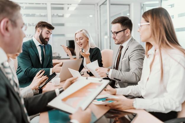 Grupo de empresários dedicados, vestidos de terno em reunião na sala de reuniões.