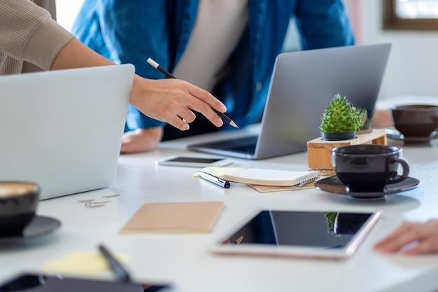 Grupo de empresários discutindo e trabalhando em um laptop sobre a mesa do escritório