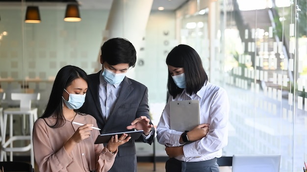Grupo de empresários em máscara protetora usando tablet digital e discutindo estratégia de negócios na sala de conferências.