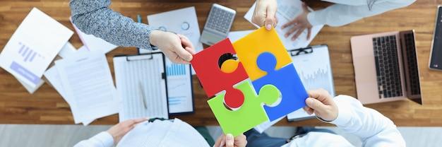 Grupo de empresários está sentado à mesa e montando uma vista superior de quebra-cabeça colorido