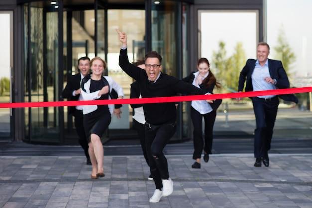 Grupo de empresários felizes correndo de um prédio comercial cruzando a linha de chegada da fita vermelha