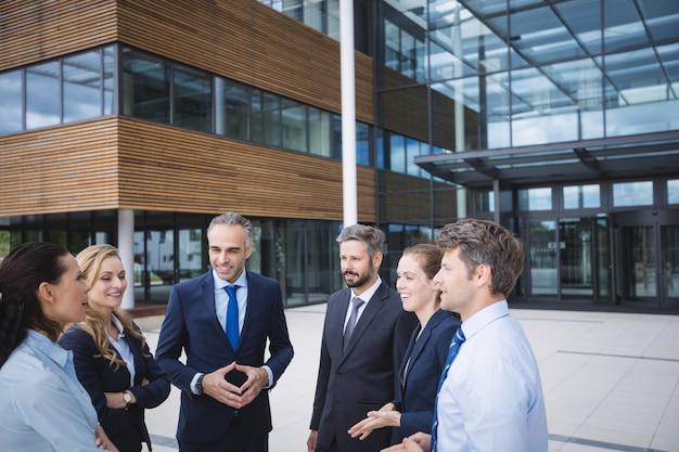 Grupo de empresários interagindo fora do prédio de escritórios