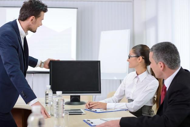 Grupo de empresários masculinos e femininos, sentado em uma mesa.