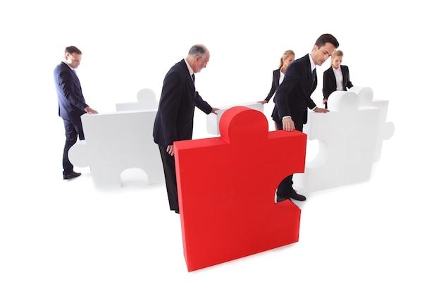 Grupo de empresários montando quebra-cabeça isolado no fundo branco
