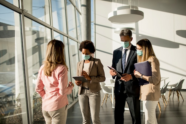 Grupo de empresários multiétnico tem uma reunião e trabalha no escritório enquanto usa máscara como proteção contra o coronavírus
