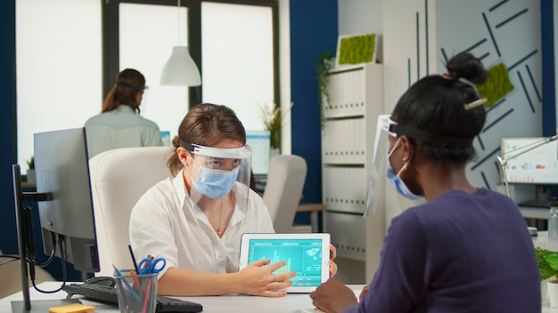 Grupo de empresários multiétnicos confiantes com máscaras, analisando dados usando tablet digital enquanto estão sentados no escritório com o novo normal. colegas que trabalham em segundo plano, respeitando a distância social