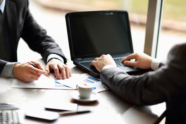 Grupo de empresários ocupados discutindo questões financeiras durante a reunião