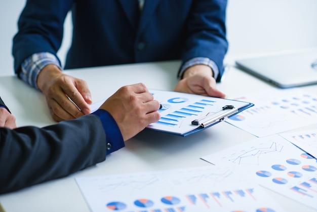 Grupo de empresários ocupados discutindo questões financeiras durante uma reunião no escritório.