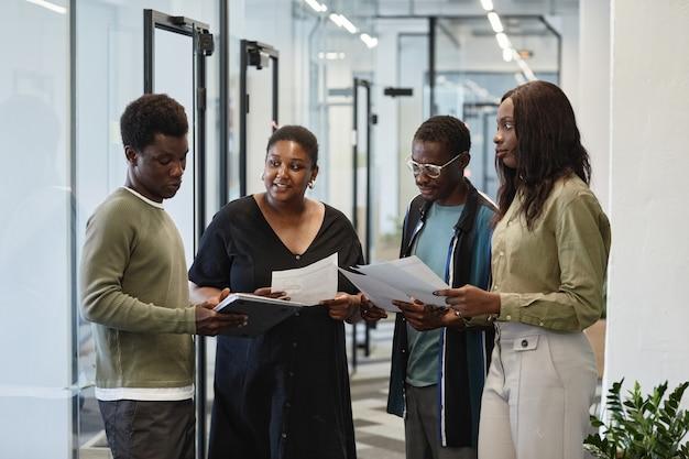 Grupo de empresários ouvindo a ideia de um colega mostrando relatório no computador tablet