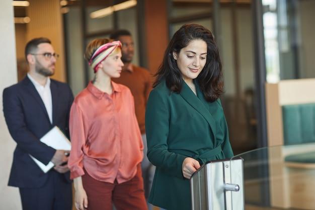 Grupo de empresários passando pelo portão automático ao entrar no prédio comercial, foco em jovem mulher do oriente médio passando o cartão de identificação, copie o espaço