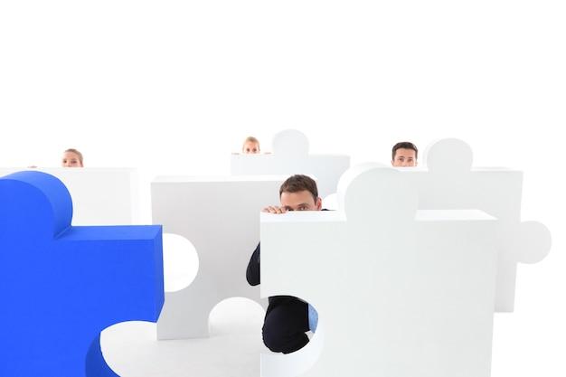 Grupo de empresários se escondendo atrás de um quebra-cabeça isolado no fundo branco