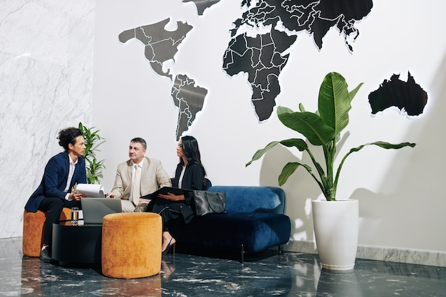 Grupo de empresários se reunindo em um escritório moderno, discutindo planos e ideias