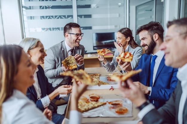 Grupo de empresários sentados na sala de reuniões, conversando, rindo e comendo pizza no almoço.