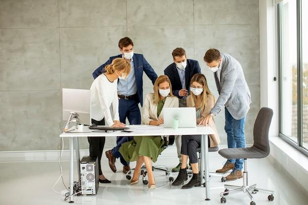 Grupo de empresários tem reunião e trabalho no escritório e usa máscaras como proteção contra coronavírus