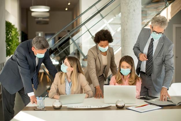 Grupo de empresários tem uma reunião e trabalho no escritório e usa máscaras como proteção contra o vírus corona