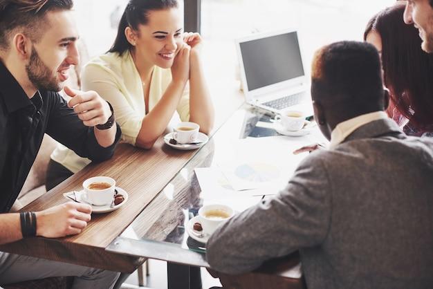 Grupo de empresários trabalhando usando um laptop e segurando um documento