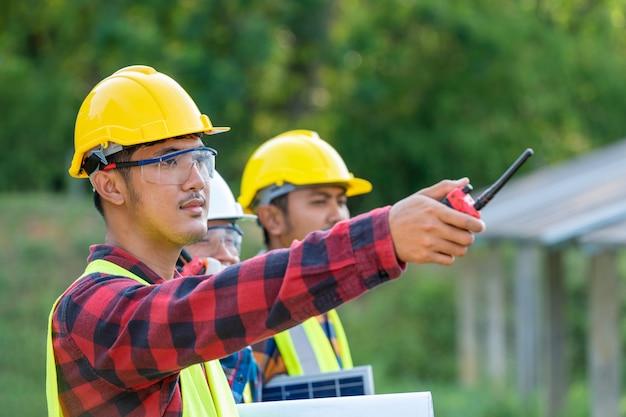 Grupo de engenheiro que trabalha na verificação e manutenção com baterias solares perto de painéis solares em dia de sol na estação de usina de energia solar.